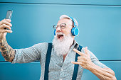 istock Senior crazy man taking self video while listening music with headphones - Hipster guy having fun using mobile smartphone playlist apps - Happiness, technology and elderly lifestyle people concept 1151608269