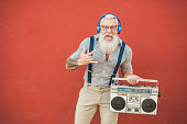 istock Senior crazy man with boombox stereo playing rock music - Trendy mature guy having fun dancing with vintage radio - Joyful elderly lifestyle concept - Focus on his face 1137525990