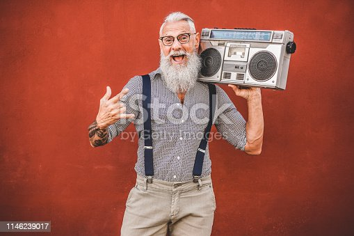 Senior crazy man with boombox stereo playing rock music - Trendy mature guy having fun dancing with vintage radio - Joyful elderly lifestyle concept - Focus on his face