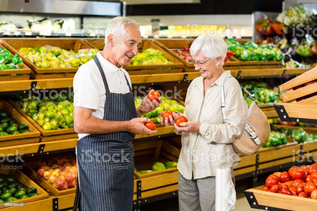 Ältere Kunden und Arbeitnehmer diskutieren Gemüse – Foto