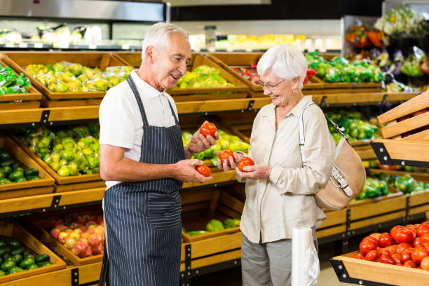 Senior customer and worker discussing vegetables stock photo