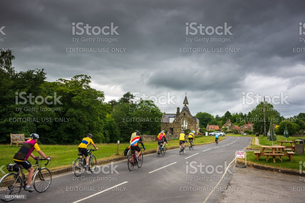 Senior cyclists make their way through the charming village of Hutton-Le-Hole in North Yorkshire royalty-free stock photo