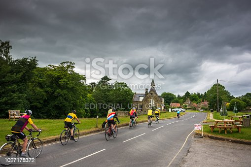 A group of senior male cyclists are on the move through the charming village of Hutton-Le-Hole in North Yorkshire.