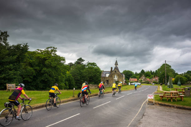 Senior cyclists make their way through the charming village of Hutton-Le-Hole in North Yorkshire stock photo