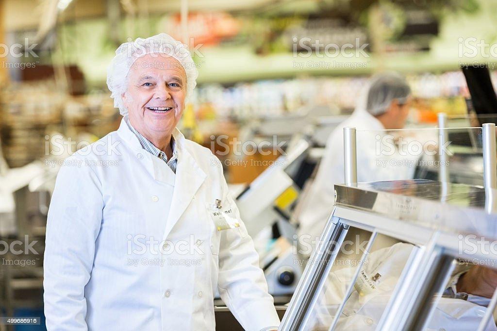 Senior deli manager lächelnd während der Arbeit in einem Supermarkt – Foto