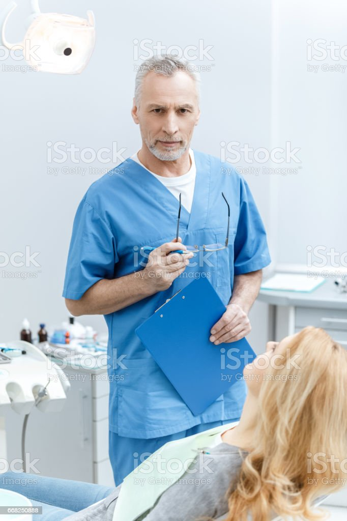 senior dentist in uniform talking with patient in dental clinic foto stock royalty-free