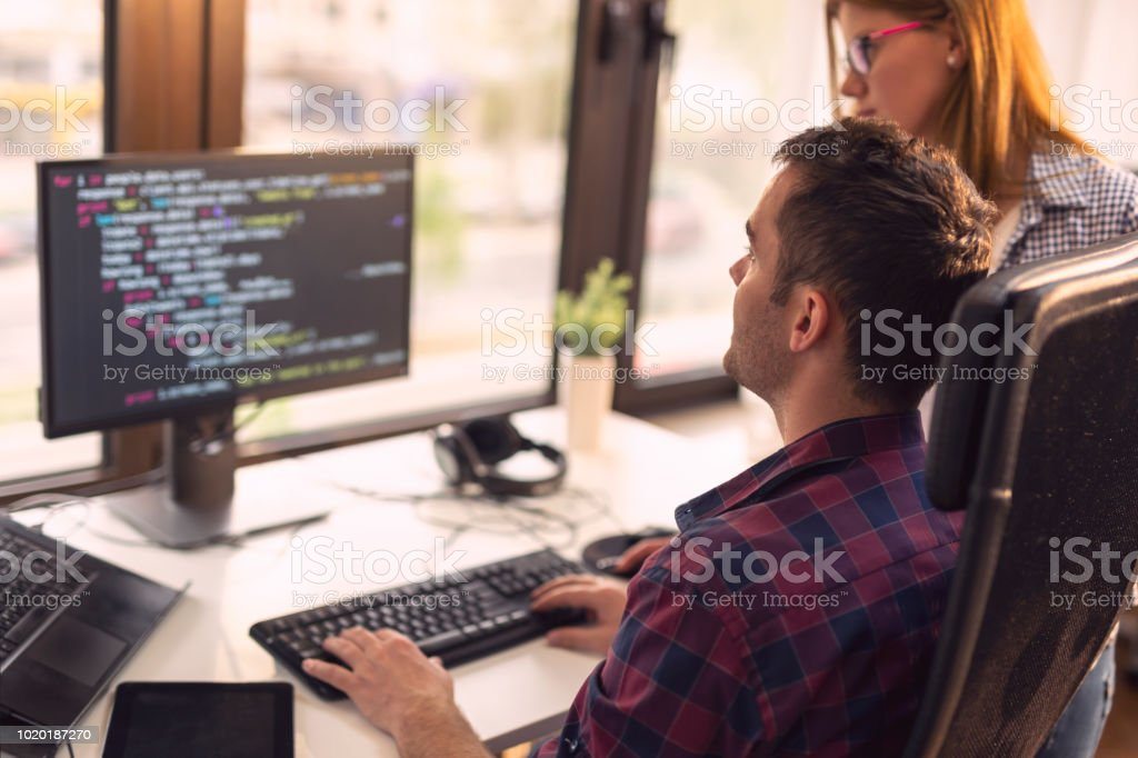 Senior developers working Two senior developers working in a software developing company office. Focus on the man sittig Adult Stock Photo