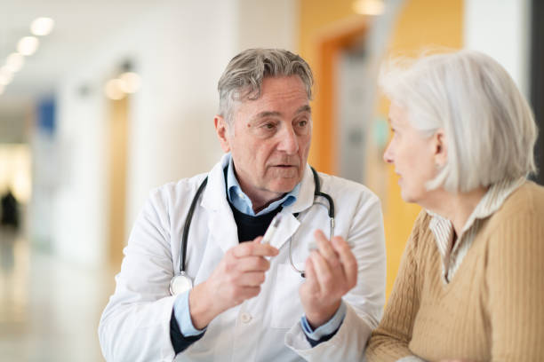 Senior diabetes patient A  male doctor is having a medical consultation with his senior Caucasian female patient in a hospital. He is teaching her how to use an insulin pen and she is very attentive. hypoglycemia stock pictures, royalty-free photos & images