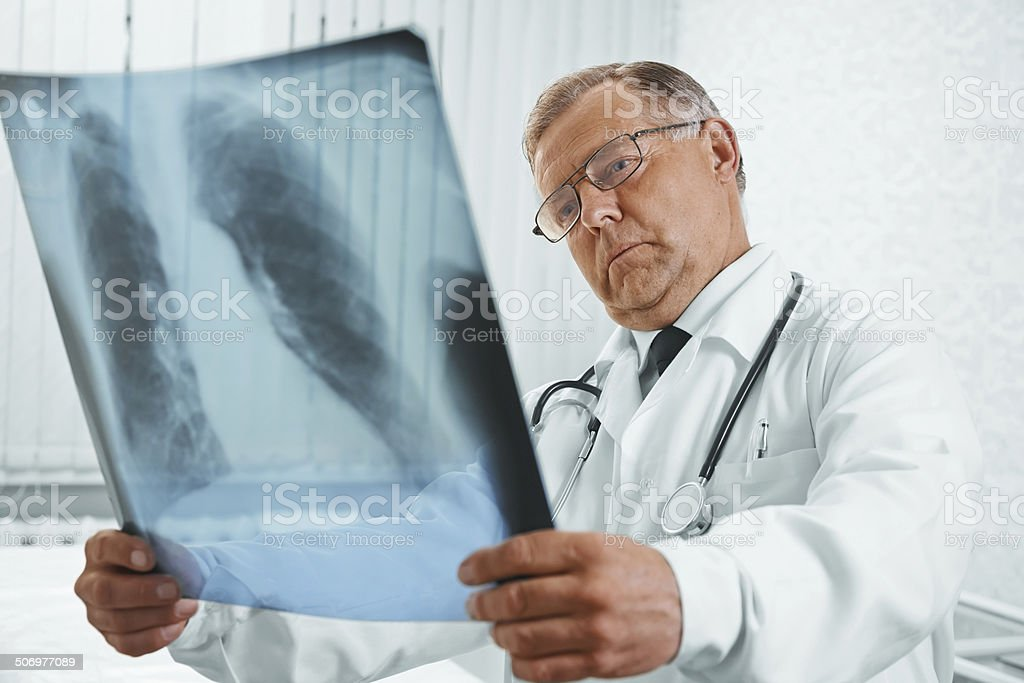 Senior doctor examines x-ray image stock photo