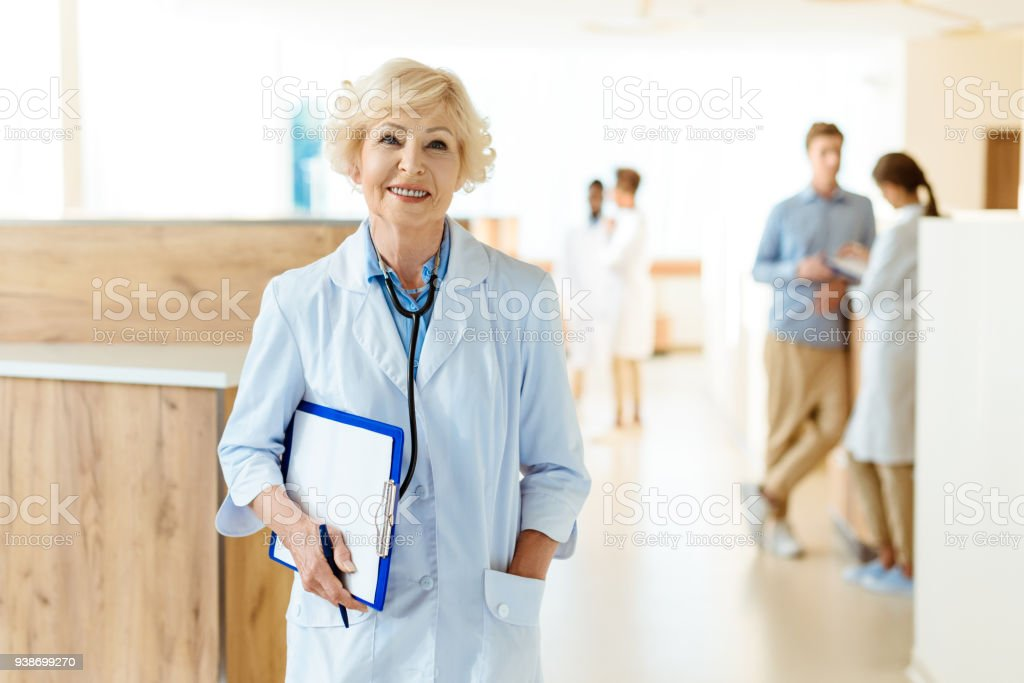 Senior doctor in lab coat standing in hospital hall and holding a...