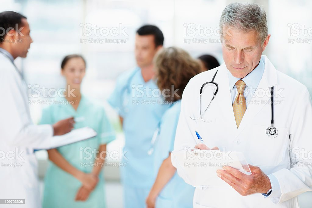 Senior doctor noting something with his blur team in background royalty-free stock photo