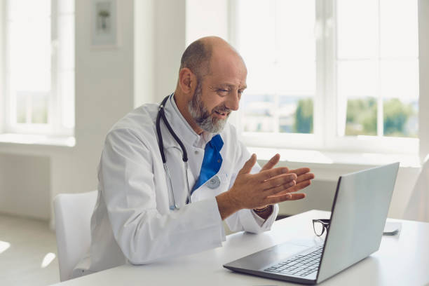 Senior doctor speaks with patient using laptop online video webinar consultation sitting in clinic office. Telemedicine. stock photo