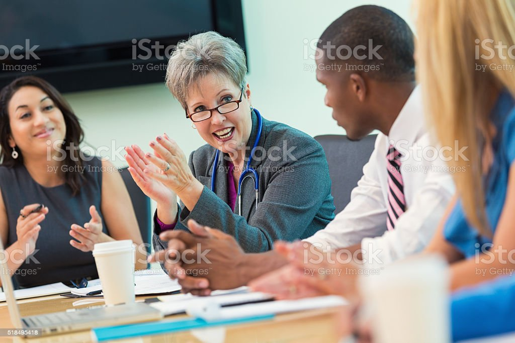 Senior doctor talks in hospital board meeting stock photo