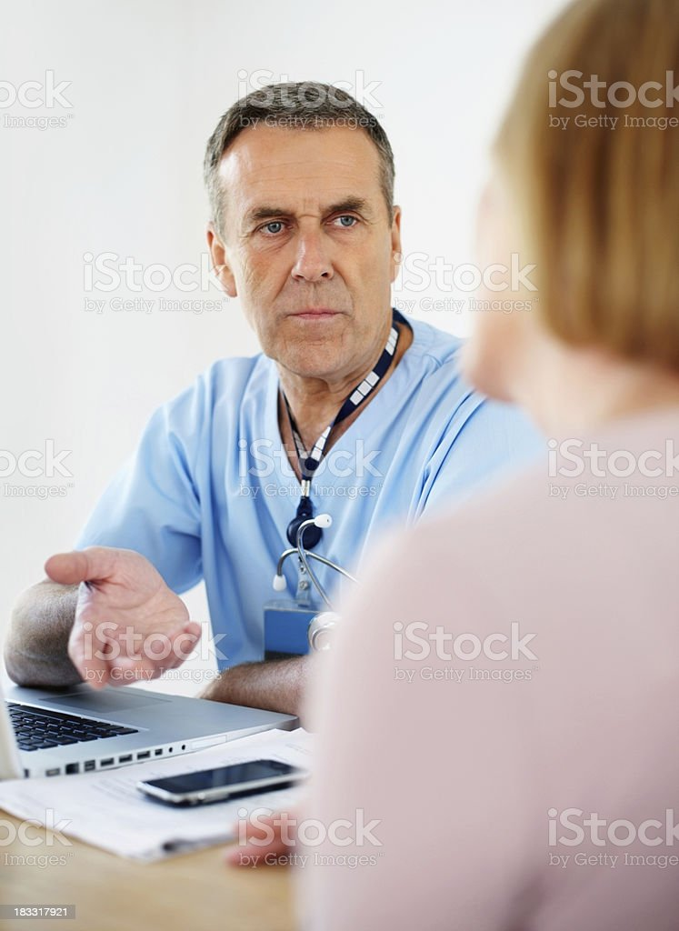 Senior doctor with laptop on desk consulting female patient royalty-free stock photo