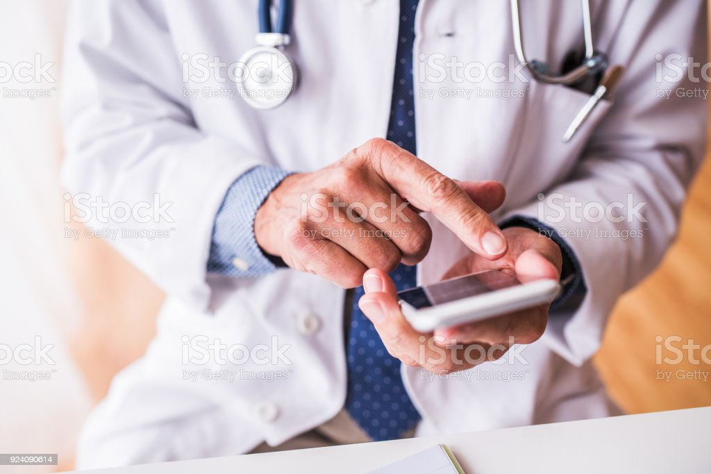 Senior doctor with smartphone working at the office. stock photo