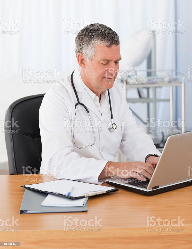 Senior doctor working on his laptop royalty-free stock photo