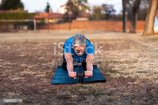 istock Senior doing workout with ab roller outdoors 1069500176
