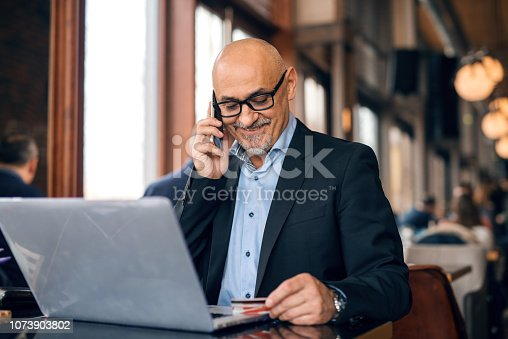 Senior dressed in suit using smart phone and credit cart for on-line shopping. Cafe interior.
