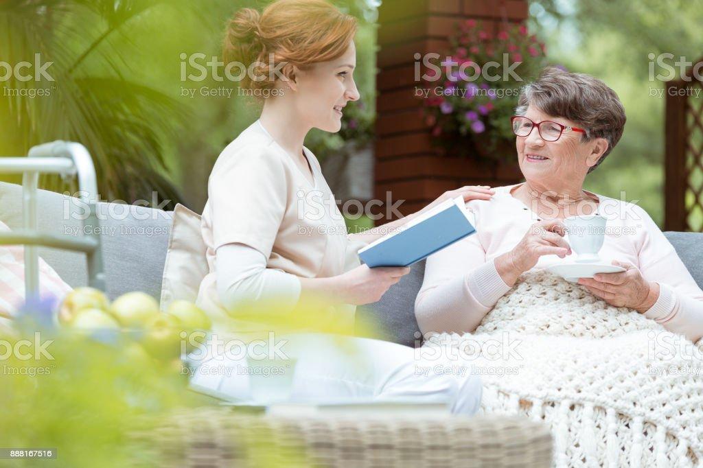 Senior drinking tea in garden stock photo