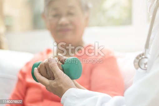 istock Senior elderly Asia woman with medical caregiver or physical therapist helping patient holding dumbbell in physical therapy session. Healthy old people concept. 1140076522