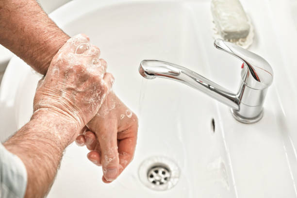 Senior elderly man his hands with soap under tap water faucet, detail photo. Hygiene illustration concept during ncov coronavirus / covid-19 outbreak prevention stock photo