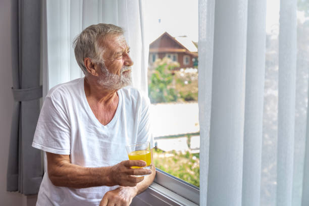 senior elderly man standing and looking out of window in bedroom after waking up in morning with juice - old men window imagens e fotografias de stock