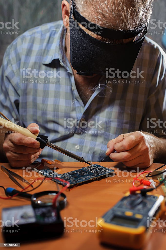 Senior electrician with soldering iron foto stock royalty-free