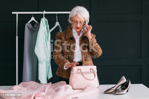 1133515238 istock photo senior elegant lady glamor lifestyle pink outfit 1132968129
