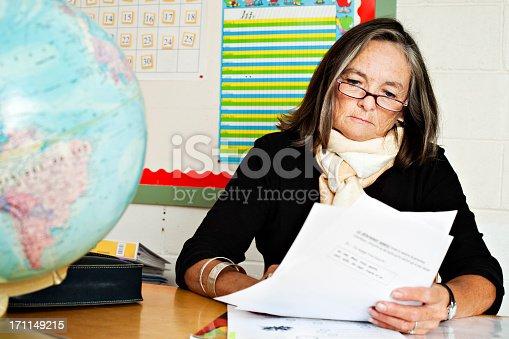 868148212 istock photo Senior elementary teacher correcting homework 171149215