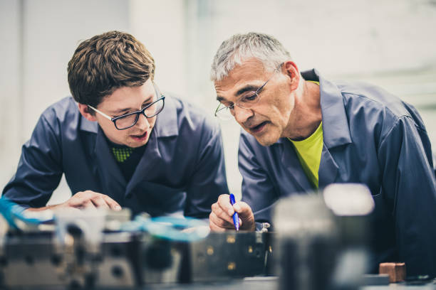 Senior engineer explaining machine functioning to his student Senior engineer mentoring his student by explaining the functioning of a machine and pointing to its parts. mechanical engineering stock pictures, royalty-free photos & images