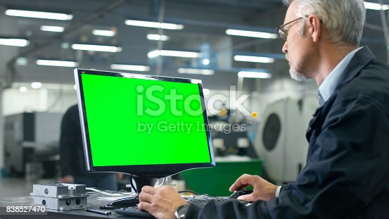 istock Senior engineer in glasses is working on a desktop computer with a green screen on monitor in a factory. 838527470