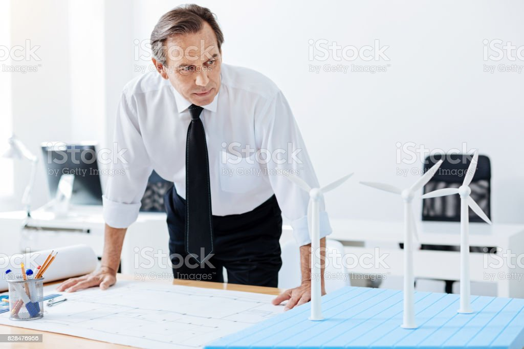 Senior engineer looking at windmill models stock photo