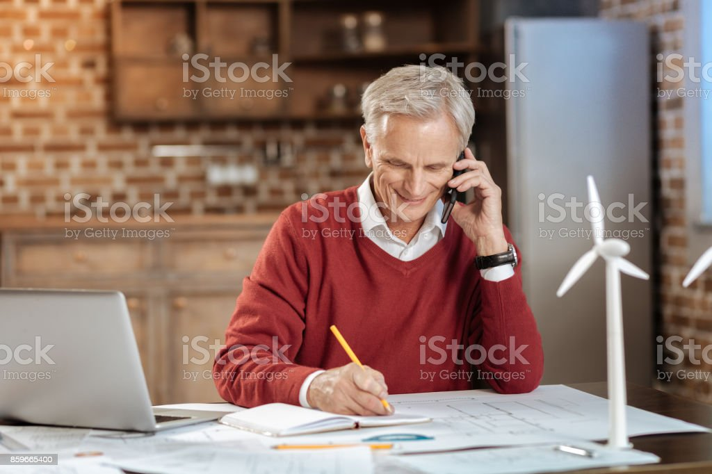 Senior engineer talking on the phone and making notes stock photo