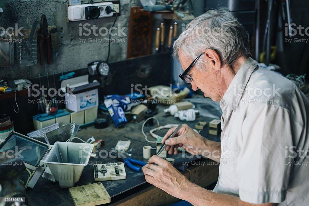 Senior engineer working in garage stock photo