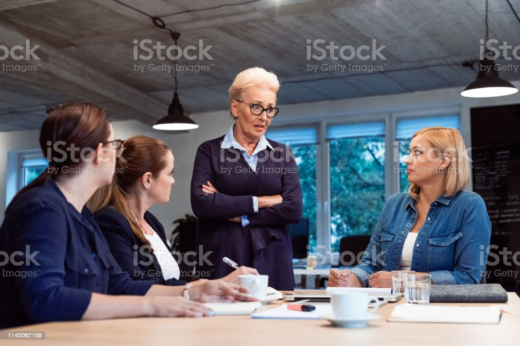 Senior entrepreneur discussing with colleagues Confident senior businesswoman discussing with colleagues. Female professional listening to elderly role model. They are working on start-up business. 35-39 Years Stock Photo