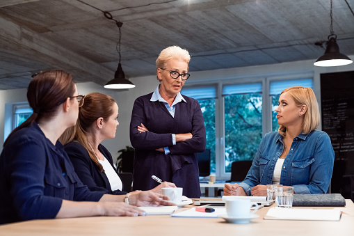 Senior Entrepreneur Discussing With Colleagues Stock Photo - Download Image Now