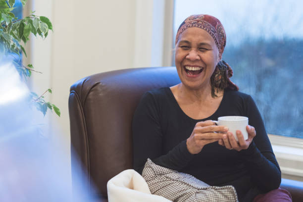 Senior ethnic woman with cancer sits by her window drinking tea stock photo