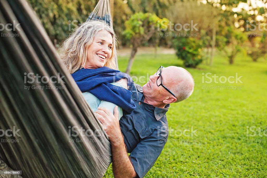 Senior european couple talking lying downin a hammock stock photo