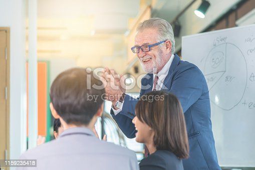 istock Senior Executive boss is congratulating team in office meeting for business success 1159235418