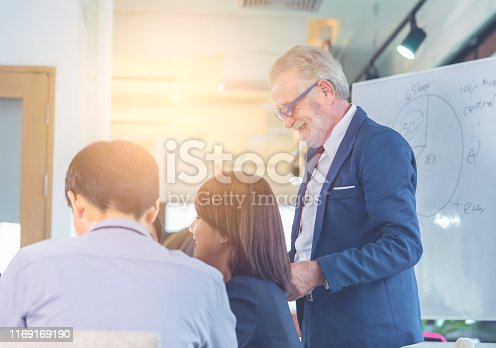 istock Senior Executive boss is congratulating team in office meeting for business success 1169169190