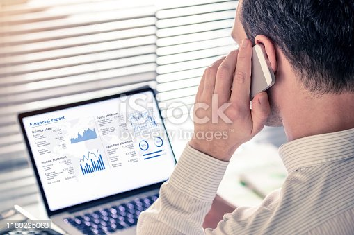 1068812018istockphoto Senior executive manager analysing a financial report on computer in office and calling on the phone, working with operations data and kpi: balance sheet, income statement, equity. Consultant audit 1180225063