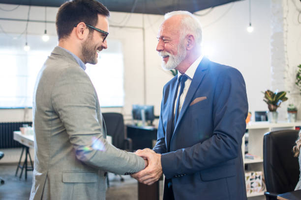 Senior executive shaking hands with young employee at office stock photo