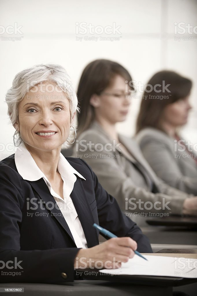 Senior executive taking notes at a presentation stock photo