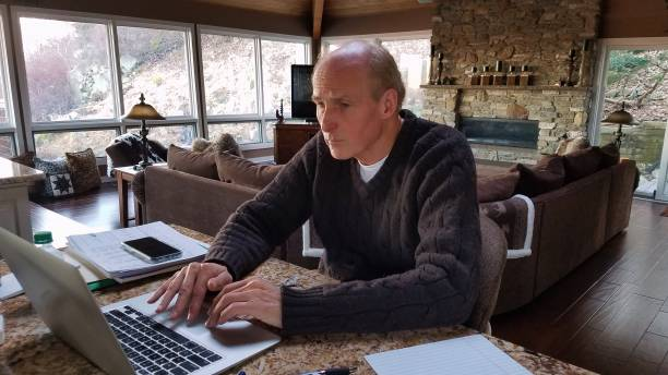 Senior Executive/Entrepreneur Working From a Rustic Style Home on a Laptop stock photo