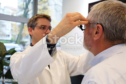 Doctor measuring eyesight with his equipment on a senior man.