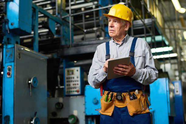 senior-fabrik arbeiter mit tablet - altbau stock-fotos und bilder