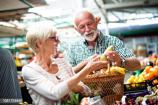 Senior couple choosing bio food fruit and vegetable on the market during weekly shopping
