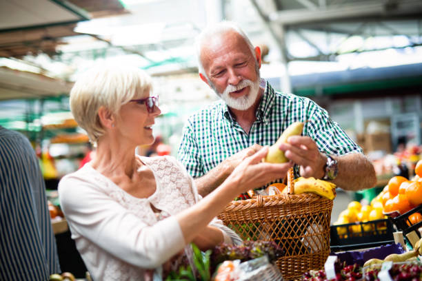 senior family couple choosing bio food fruit and vegetable on the market during weekly shopping - targ handel detaliczny zdjęcia i obrazy z banku zdjęć
