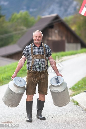 Senior Farmer Carrying Containers for Milk on a Farm in Julian Alps - Stock Photo