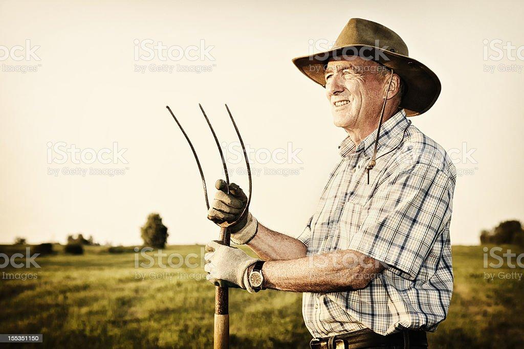 Senior farmer holding pitchfork royalty-free stock photo